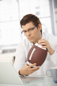 Businessman concentrating on work holding football