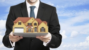 businessman holding house