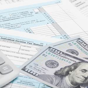 US Tax Form 1040 with calculator and dollars - 1 to 1 ratio