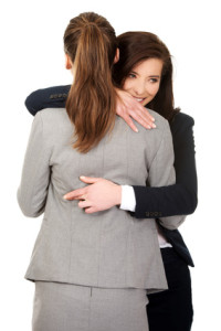 Businesswoman embrace woman with fingers crossed.