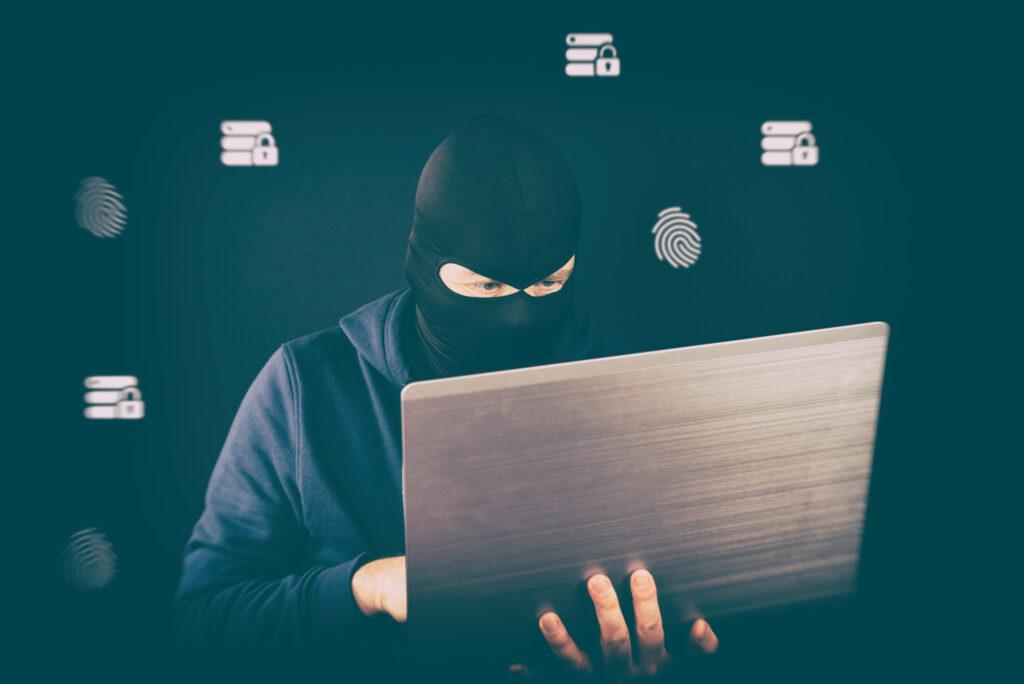 Sur un fond noir, un criminel masqué sur un ordinateur portable pirate les emails, empreintes digitales et cadenas en fond