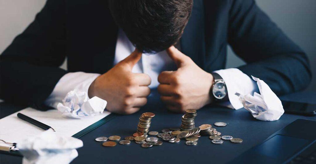homme desespéré, piles de pièces, procédure de faillite, Chapitre 7 vs Chapitre 11