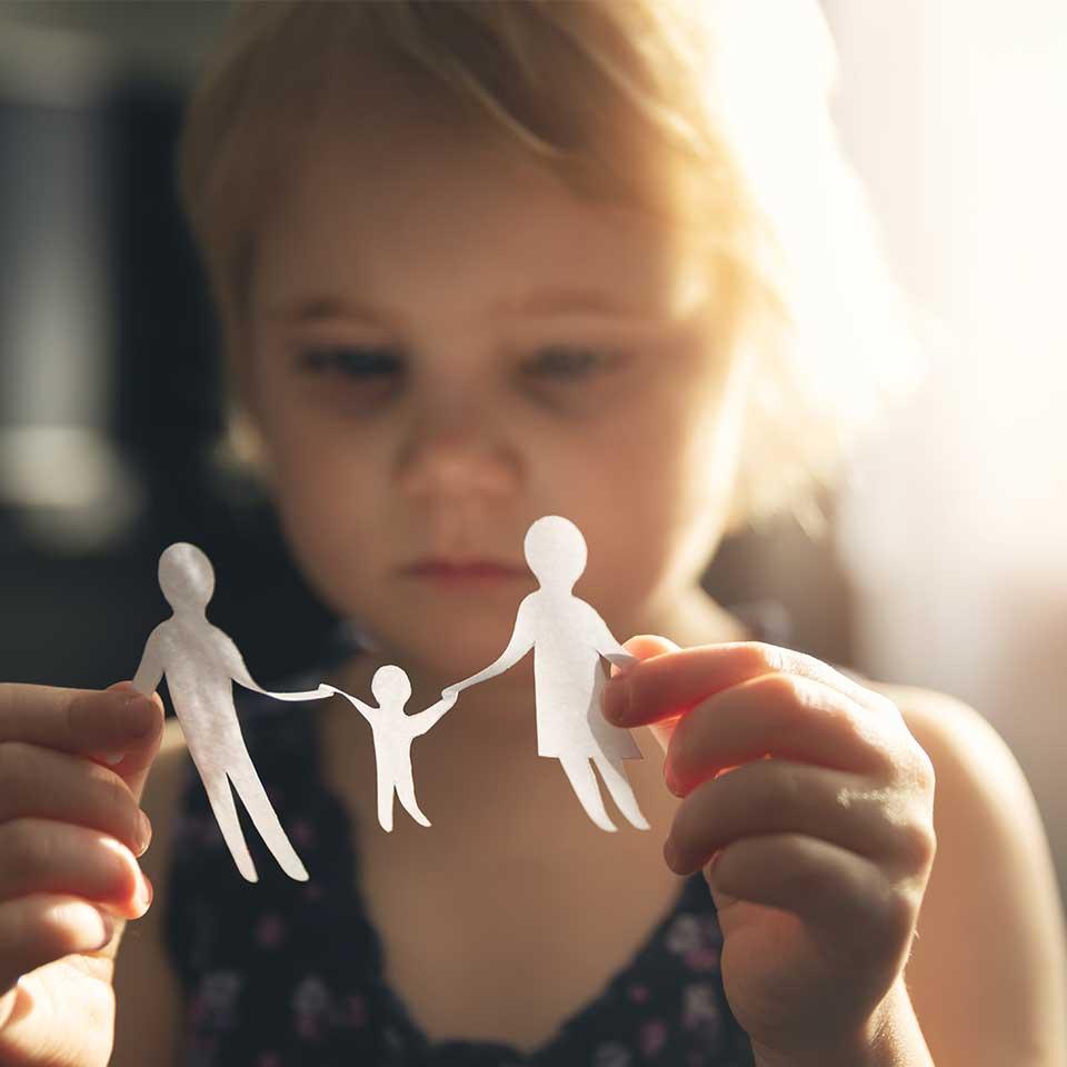 Enfant tenant une guirlande famille en papier, garde d'enfant international, enlèvement d'enfant international par parents