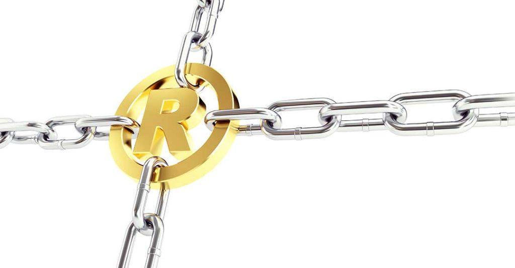 Symbole marque déposée en or tenu par des chaines, intention volontaire dans la violation des marques