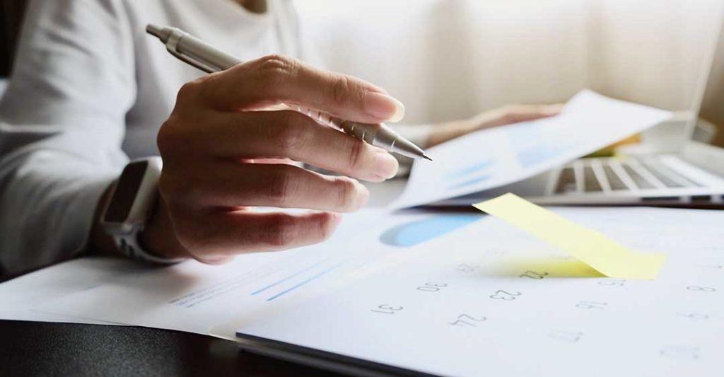 homme d'affaires avec un stylo créant un rapport annuel, obligation de rapport annuel en Floride et délais, agent enregistré Floride, services d'agent enregistré, résumé annuel de Floride, agent enregistré