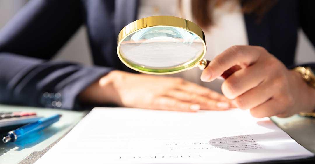 femme d'affaires avec une loupe, regardant un document, pourquoi les fautes de frappe et de grammaire dans un contrat peuvent être désastreuses